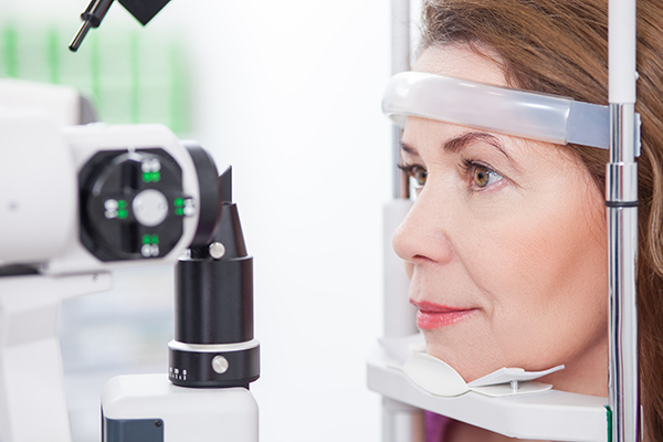 Cheerful woman is having eye examination at the slit lamp in optometrist lap